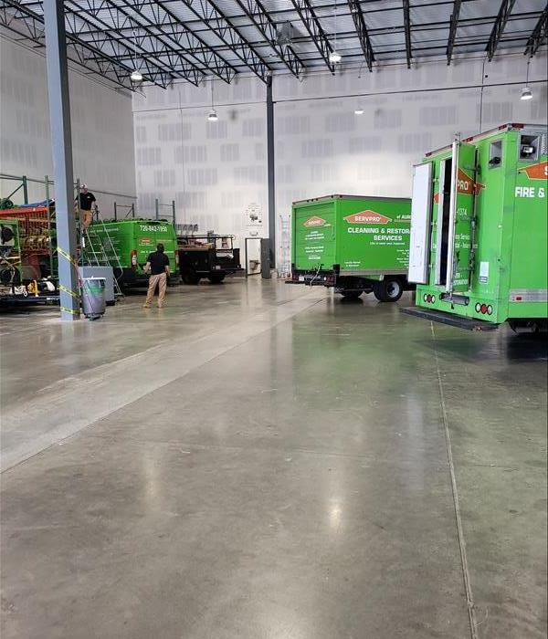 Warehouse space with three green trucks parked